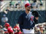 Cleveland Indians' Corey Kluber, right, waits for a new baseball after giving up a home run to Cincinnati Reds' Todd Frazier, left, during the second inning of a spring training baseball game Tuesday in Goodyear, Ariz.