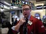 Trader Ryan Falvey talks on his mobile phone headset as he works on the floor of the New York Stock Exchange, today.
