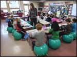First-grade teacher Kim Baum conducts a lesson as her students sit on stability balls at Frank Elementary School in Perrysburg. The inflatable balls, usually found in gyms and fitness centers, are said to help students better focus on their school work because they can move around without having to leave their seats, she says.