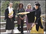 First lady Michelle Obama, second from left, watches a Noh performance by local college students, with monk of Kiyomizu-dera Buddhist temple, Eigen Onishi, left, U.S. Ambassador to Japan Caroline Kennedy, second from right,  at the temple in Kyoto, Japan, today.