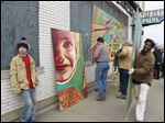 Ryan Klempner, 15, leans against the wall next to an artist's rendition of his face as members of the Old West End Neighborhood Initiatives install a mural on the Parisian Cleaners building on Detroit Avenue in Toledo.