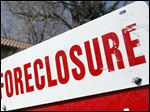 A foreclosure sign sits atop a for sale sign in front of a single-family home.