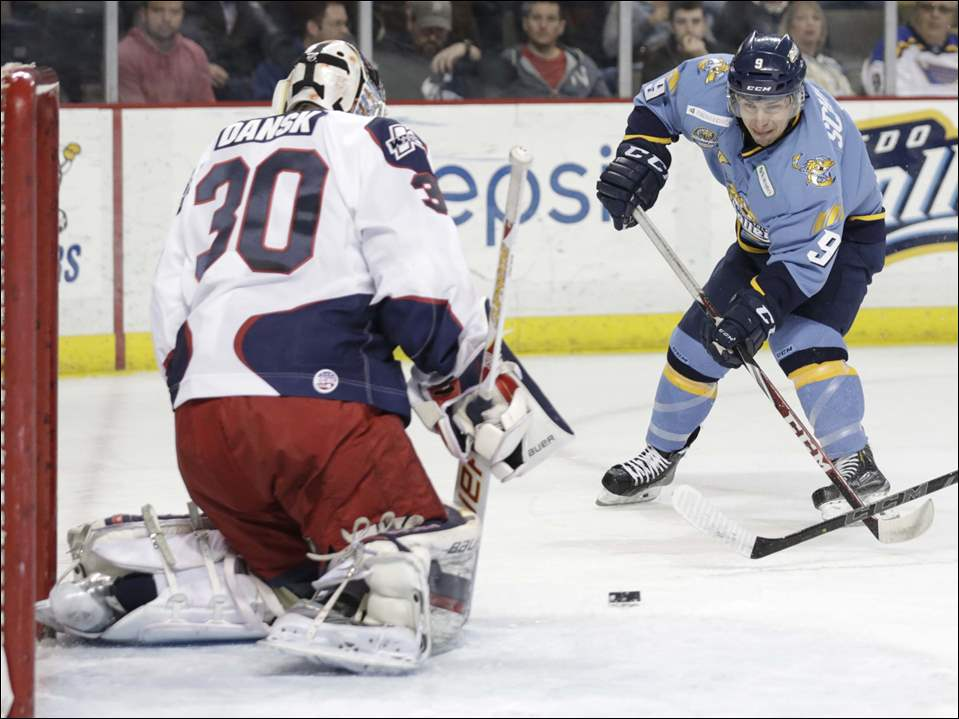 Toledo Walleye player Troy Schwab (9) looks for the rebound shot against Kalamazoo K-Wings goalie Oscar Dansk (30).
