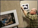 Bedford High School art teacher Jason Sanderson hangs student art for the upcoming show at the Bedford library.