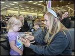 Peyten Young, a Perrysburg High senior, puts a temporary tattoo on Olivia Berry, 2, during an Easter Fun! event at Books-A-Million at Levis Commons.