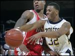 Toledo's Anton Currie, right, passes during a 2006 NCAA college basketball game against Ball State in Toledo, Ohio. Currie pleaded guilty to conspiracy in a decade-old points shaving scandal and admitted accepting cash and other incentives to alter his performance at the University of Toledo.
