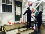 Toni Williams, 28, left, and Natasha Bell, 30, leave balloons at a town home in Detroit, Wednesday, the frozen bodies of a boy and girl were found in a deep freezer.
