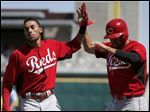 Cincinnati Reds' Billy Hamilton, left, and Kristopher Negron congratulate each other after they both scored runs.