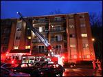 Firefighters work at the scene of a fire at King Towers apartment complex inn Cincinatti that took the life of Cincinatti firefighter Daryl Gordon, Thursday.