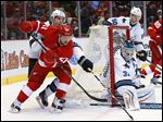 Detroit Red Wings left wing Tomas Tatar (21) passes the puck as San Jose Sharks defenseman Justin Braun (61) defends near goalie Antti Niemi (31) during the second period.