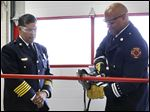 Above, Chief Luis Santiago looks on as Toledo fire Capt. Steven Lewis uses a hydraulic cutting tool during the 'ribbon cutting' portion of the dedication ceremony for the new Fire Station 12 at 3435 Chase St. in North Toledo.
