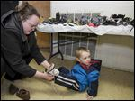 Amber Miller of Toledo finds a pair of shoes for her son Devlan Miller, 2.