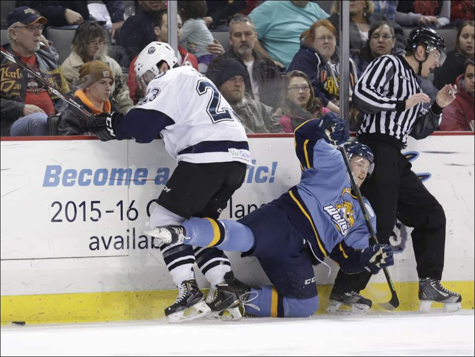 Toledo Walleye player Reed Seckel (42) is knocked into an official by Evansville Icemen player Zack Currie (23).