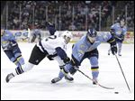Toledo Walleye player Tyler Barnes (7) skates the puck past Evansville Icemen player Colin Murray (12).