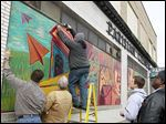 Mike Sachs installs a mural on the Parisian Cleaners building on Detroit Ave. in Toledo.