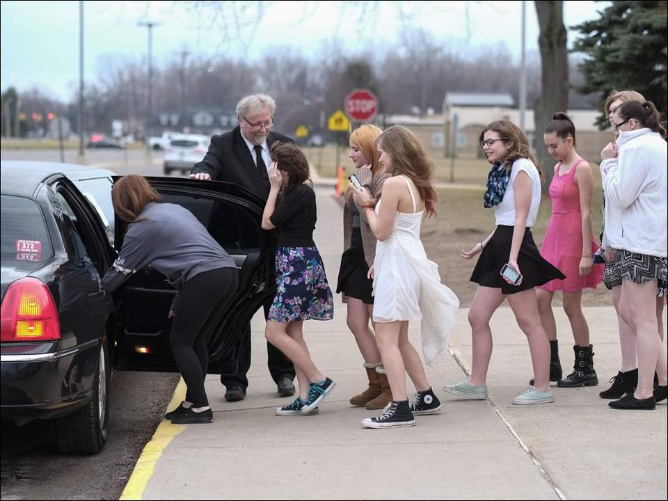Jeff Winters, a limousine driver with Childers, holds the door open as eighth-grade girls pile in for a ride during a film festival at Bedford Junior High School.
