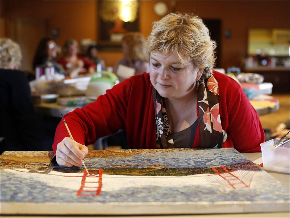 Local artist Amy Pollman of Sylvania works on a mosaic 'Magazine Collage of the Golden Gate Bridge.'