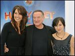 Susan Schneider, left, Robin Williams, and Zelda Williams arrive at the premiere of
