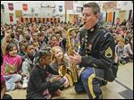 Staff Sgt. David Parks of the U.S. Army Field Band Saxophone Quartet blows on his tenor sax while Cedria Jaynes presses the keys during a children's music clinic Monday at Greenwood Elementary School in Toledo.