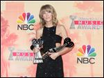 "Taylor Swift poses in the press room with the awards for best lyrics for ""Blank Space"", song of the year for ""Shake It Off"" and artist of the year at the iHeartRadio Music Awards at The Shrine Auditorium on Sunday in Los Angeles."
