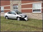 A damaged vehicle sits along side Bowsher High School after sideswiping the building.
