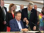 Ohio Governor John Kasich hands a pen to State Senator Randy Gardner as they signs Senate Bill 1.