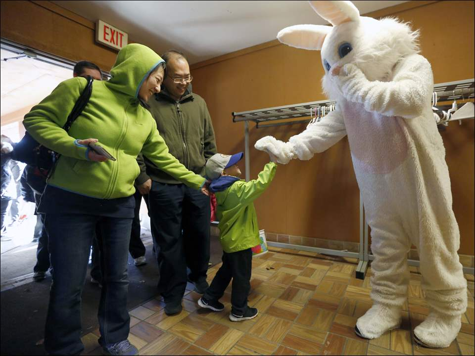 The Easter Bunny, played by Brent Tary, right, greets guests including Joshua Zhang, 3, center, and his parents Weina Zhang, left, and Yue Zhang, right.