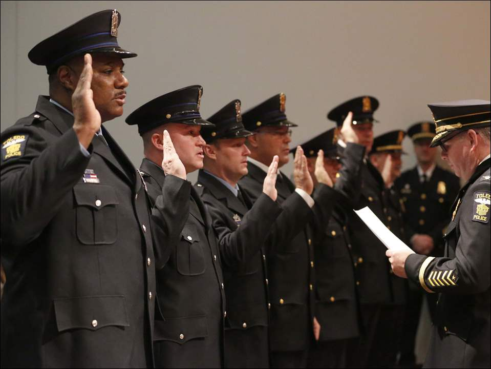 Toledo Police George Kral, right, swears in Toledo Police Officers to their promotion rank.
