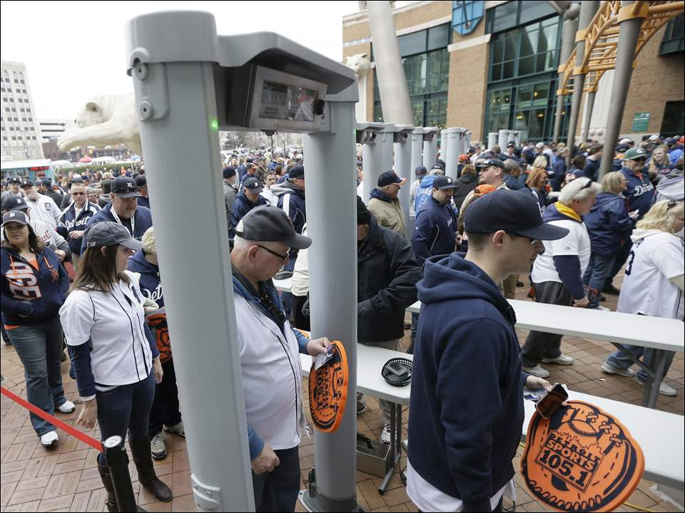 Baseball fans pass through metal detectors before entering Comerica Park.