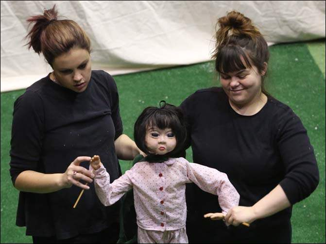 Puppeteers Becky Perry, left, and Megan Aherne, right, work together to operate The Little Girl, the star of the show, during a rehearsal.