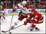 Carolina Hurricanes defenseman Ron Hainsey, left, and Red Wings left wing Teemu Pulkkinen battle for the puck in the second period.