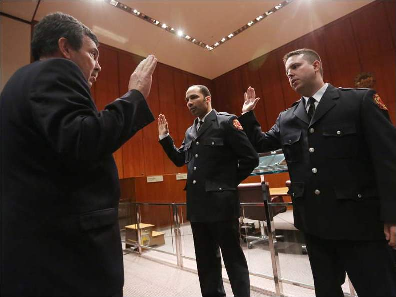 Retired Toledo Fire and Rescue Department CFO Dave Dauer, left,  swears in newly promoted lieutenants Adam Klugh and Tony Santiago, right.