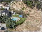 A home with a swimming pool in Altadena, Calif., is near a hillside without vegetation because of the state's severe drought.