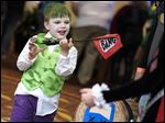 Masquerading as the Joker, one of Batman's arch-enemies, Zak Batey, 5, of Bellevue, Ohio, plays with his toy gun.