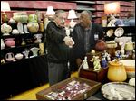 Ron Metter, left, and Bearl Moses sell antiques in their Aunt El's Attic booth during the 14th annual Antiques in April Show and Sale at Monroe County Community College in Monroe. The show featured 55 booths.
