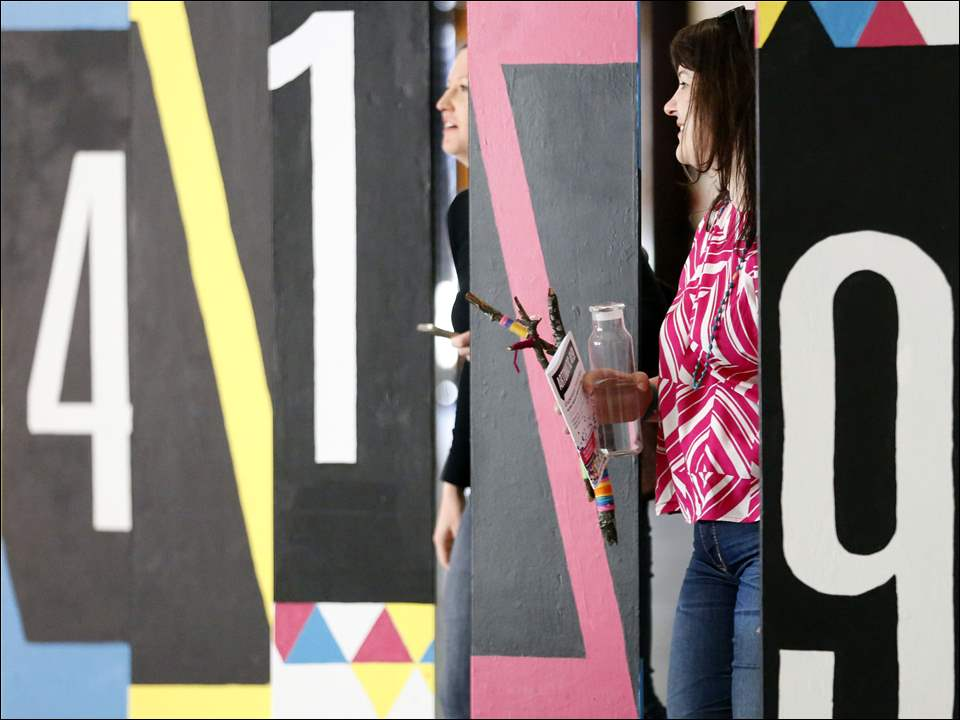 Valerie Vetter, left, and Jessica Lashley, right, from Maumee, walk through a big 419 sign during  Artomatic 419! Toledo's showcase of visual and performing arts at One Lake Erie Center on April 11, 2015. The event was featured on three floors with 300 people showing and discussing their work.