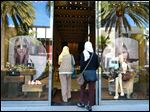 Women enter a high end fashion store on Rodeo Drive in Beverly Hills, Calif.