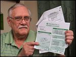 CTY bills12  James Markin (cq) of Toledo poses at his home Tuesday, April 7, 2015, with ProMedica medical bills he incurred due to a visit to the Flower Hospital emergency room.  The Blade/Dave Zapotosky.