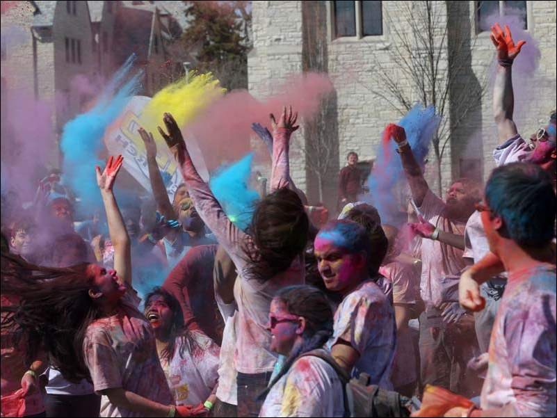 "Students scream as they toss colored powder into the air in a ""color blast"" during celebration of the Hindu holiday Holi at the University of Toledo Wednesday."