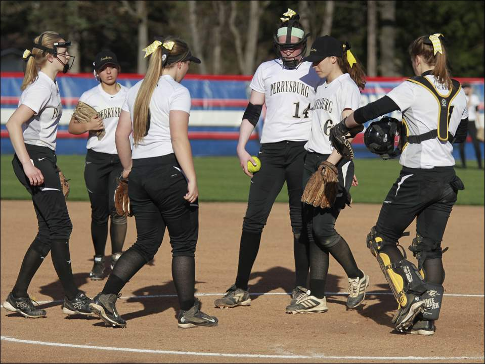 Perrysburg pitcher Kate Rudebock is met on the mound by teammates.