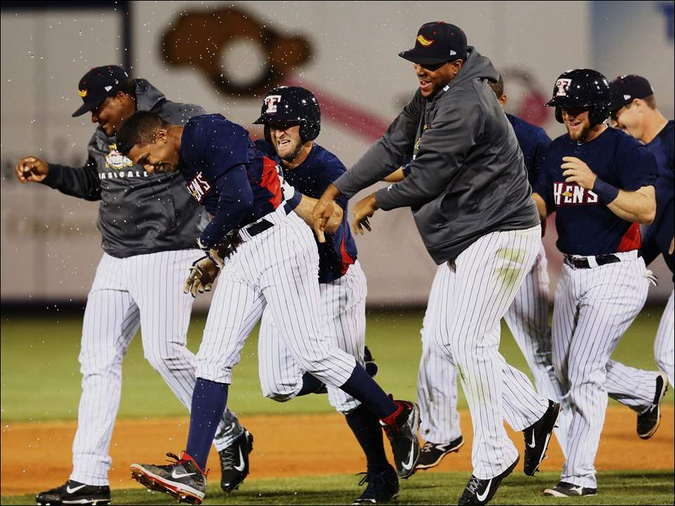 Toledo Mud Hens players swarm SS Dixon Machado after he drove in the game-winning run.