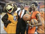 Michael Huger and his son Michael II, 3, and wife Tonya pose with Frieda the Falcon earlier today at the Stroh Center.