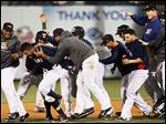 The Mud Hens players swarm shortsop Dixon Machado after he drove in the game-winning run on a grounder up the middle in the bottom of the seventh inning in the second game Thursday at Fifth Third Field.