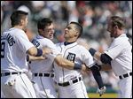 Detroit's Nick Castellanos, left, Ian Kinsler, and pinch runner Andrew Romine, right, celebrate with Jose  Iglesias after the shortstop knocked in the game-winning run with a single with one out in the bottom of the ninth inning.
