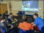 Hayden Sabovik, right, a seventh grader at Rossford Junior High, jokes with friends as they play 'Super Smash Brothers' on the Nintendo Wii at the Rossford Library.