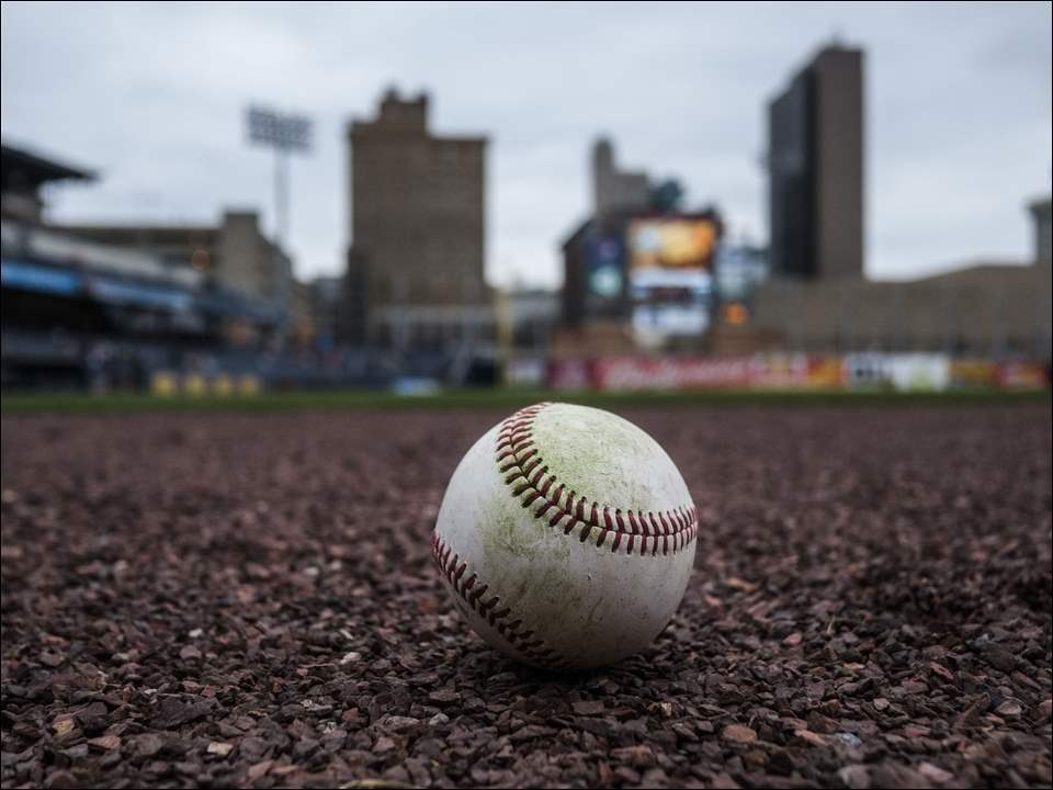 A baseball sits on the warning track during the opening day of the Toledo Mud Hens baseball team at Fifth Third Field, Thursday, April 16,  2015.