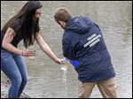 Alexa Seaman, left, a UT student and Sierra Club Clean Water Fellow, gets a sample from Todd Haggard of the city's Environmental Services Department at the Ottawa River. Monday was the start of the spring water-testing season in the Maumee River watershed.