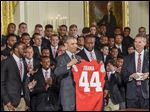 President Obama holds up an Ohio State football jersey presented to him by the Ohio State football team and coach Urban Meyer, right. The Buckeyes were honored Monday at White House for winning college football's national championship.