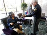 Sheriff John Tharp gives the policy to Lorinda McCalebb of the Toledo Buffalo Soldiers at One Government Center.