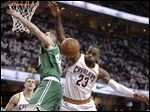 Cleveland Cavaliers' LeBron James (23) grabs a rebound over Boston Celtics' Tyler Zeller (44).